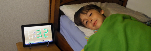 Child with Veggie Clock alongside the bed